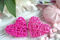 Las peonías florecen la taza rosada de melcocha en un fondo de madera blanco - imagen común de los corazones de la rota del té fotos de archivo libres de regalías