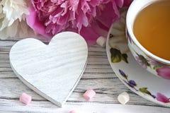Las peonías florecen la taza rosada de té con la melcocha de madera blanca en un fondo de madera blanco - imagen común del corazó Imagenes de archivo