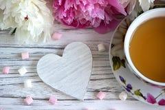 Las peonías florecen la taza rosada de té con la melcocha de madera blanca en un fondo de madera blanco - imagen común del corazó Imágenes de archivo libres de regalías