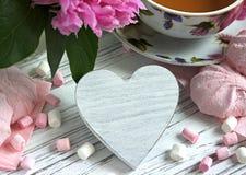 Las peonías florecen la taza rosada de té con la melcocha de madera blanca en un fondo de madera blanco - imagen común del corazó Fotografía de archivo