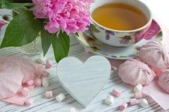 Las peonías florecen la taza rosada de té con la melcocha de madera blanca en un fondo de madera blanco - imagen común del corazó Imagen de archivo