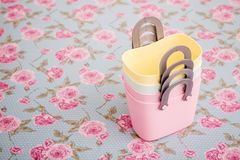 Las pequeñas bolsas de plástico decorativas coloridas con la manija en la flor Pat imagenes de archivo