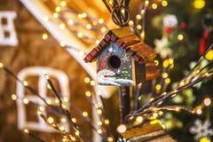 Las pequeñas casas del pájaro pintadas con los muñecos de nieve en un árbol fino adornaron la Navidad Foto de archivo