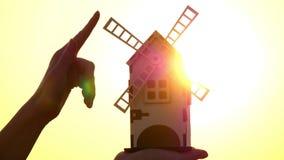 Las pequeñas cuchillas del molino de viento giran contra la perspectiva de la puesta del sol Primer de un molino decorativo en la almacen de video