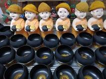 Las pequeñas estatuas lindas de los monjes budistas con limosnas ruedan foto de archivo libre de regalías