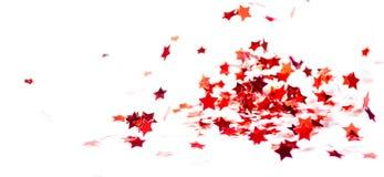 Las pequeñas estrellas brillantes rojas dispersadas del confeti vuelan Imagen de archivo libre de regalías