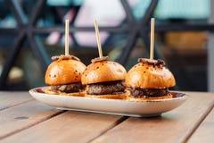 Las pequeñas hamburguesas sirvieron en una placa como aperitivos imágenes de archivo libres de regalías
