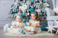 Las pequeñas hermanas abren presentes El concepto de la Navidad y de Año Nuevo Fotos de archivo libres de regalías
