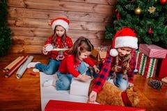 Las pequeñas hermanas divertidas felices en los sombreros de Papá Noel embalan los regalos cerca del árbol de navidad fotos de archivo