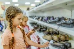 Las pequeñas hermanas eligen los zapatos fotos de archivo libres de regalías