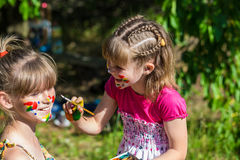 Las pequeñas hermanas felices juegan con colores en el parque, juego de niños, pintura de los niños Imágenes de archivo libres de regalías