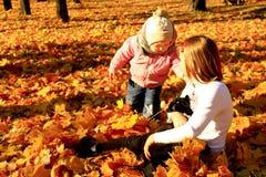 Las pequeñas hermanas juegan con su gato en el parque del otoño Fotos de archivo libres de regalías