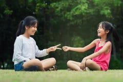 Las pequeñas hermanas son Roca-papel-Scisors para la diversión Imágenes de archivo libres de regalías