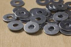 Las pequeñas lavadoras del metal dispersaron en una tabla de madera Imagen de archivo