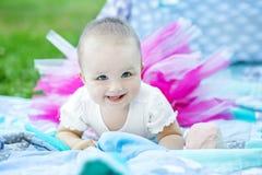 Las pequeñas mentiras y risas del bebé en la falda rosada Concepto de ch foto de archivo libre de regalías