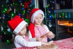 Las pequeñas muchachas lindas en los sombreros de Papá Noel cuecen el pan de jengibre Foto de archivo