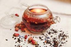Las pequeñas rosas rojas secas con el té negro en la tetera de cristal, té bebiendo, flores aromatizadas, mantel de lino; Entonad Imagen de archivo libre de regalías