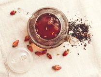 Las pequeñas rosas rojas secas con el té negro en la tetera de cristal, té bebiendo, flores aromatizadas, presentan Tableclose de Imagenes de archivo
