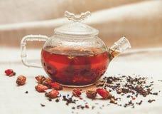 Las pequeñas rosas rojas secas con el té negro en la tetera de cristal, té bebiendo, flores aromatizadas, Tableclose de lino áspe Fotos de archivo libres de regalías