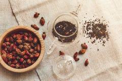 Las pequeñas rosas rojas secas en la tetera de cristal, té bebiendo, presentan Tableclose de lino áspero; Placa de madera, entona Imagen de archivo libre de regalías