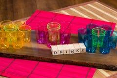 Las pequeñas tazas coloreadas en un tablero de madera con las bebidas firman Imagenes de archivo