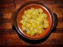 Las pequeñas uvas verdes mienten en el pote del marrón de la superaleación Fotos de archivo libres de regalías