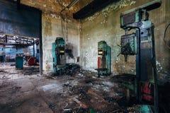 Las perforadoras industriales oxidadas viejas en taller abandonado de la fábrica parecen los robots imagen de archivo
