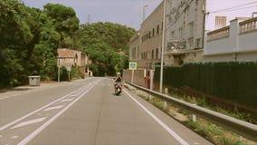 Las personas de la cara trasera dos montan en la motocicleta en el camino Muchos árboles verdes traveling Día asoleado del verano metrajes