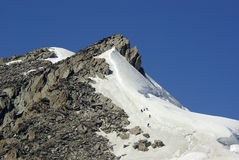 Las personas de los escaladores conquistan el pico Fotografía de archivo