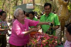 Las personas mayores que riegan la estatua de Buda el día de Songkran, Imagenes de archivo