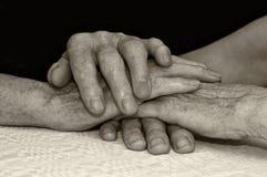 Las personas mayores sostienen cada otras las manos. Foto de archivo