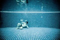 Las personas mienten debajo del agua en una piscina Imagen de archivo