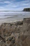 Las personas que practica surf acercan a los acantilados y a las rocas del ballybunion Foto de archivo