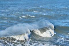 Las personas que practica surf cogen la onda grande en Nazare, equipo de la seguridad portugal Imágenes de archivo libres de regalías