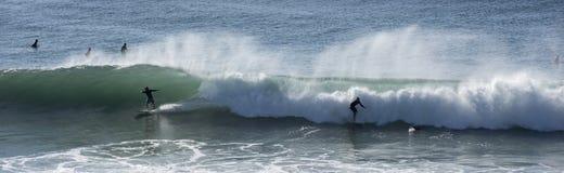 Las personas que practica surf cogen ondas grandes Imagen de archivo