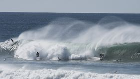 Las personas que practica surf cogen ondas grandes Foto de archivo