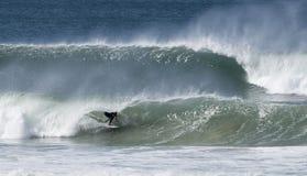 Las personas que practica surf cogen ondas grandes Imagenes de archivo