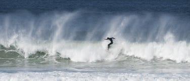 Las personas que practica surf cogen ondas grandes Fotos de archivo