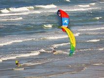 Las personas que practica surf de la cometa gozan de las ondas en la costa costa de la Florida fotos de archivo