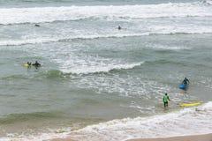 Las personas que practica surf en el Océano Atlántico varan en el Lacanau-océano, Burdeos, Imagenes de archivo