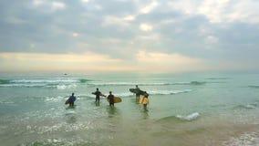 Las personas que practica surf llevan las tablas hawaianas puestas en el agua en la onda espumosa almacen de video
