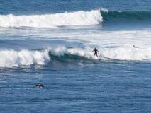 Las personas que practica surf montan las ondas Imagen de archivo libre de regalías