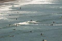 Las personas que practica surf montan ondas de la costa de Oregon Imagen de archivo libre de regalías