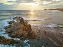 Las personas que practica surf practica surf en tiempo de la puesta del sol Fotos de archivo