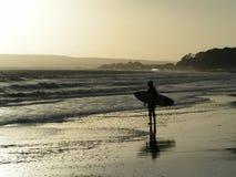 Las personas que practica surf siluetean en la puesta del sol Foto de archivo
