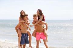Las personas sonrientes atractivas detienen a muchachas hermosas en una costa en un fondo borroso natural Imágenes de archivo libres de regalías