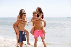 Las personas sonrientes atractivas detienen a muchachas hermosas en una costa en un fondo borroso natural Imagen de archivo libre de regalías