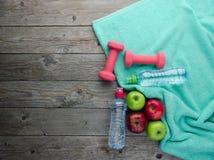 Las pesas de gimnasia coloreadas de las manzanas se divierten las botellas de agua y el towe de la turquesa foto de archivo libre de regalías