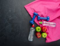 las pesas de gimnasia coloreadas de las manzanas se divierten las botellas de agua y la toalla púrpura en fondo concreto negro foto de archivo
