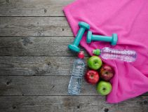 Las pesas de gimnasia coloreadas de las manzanas se divierten las botellas de agua y la toalla rosada fotos de archivo